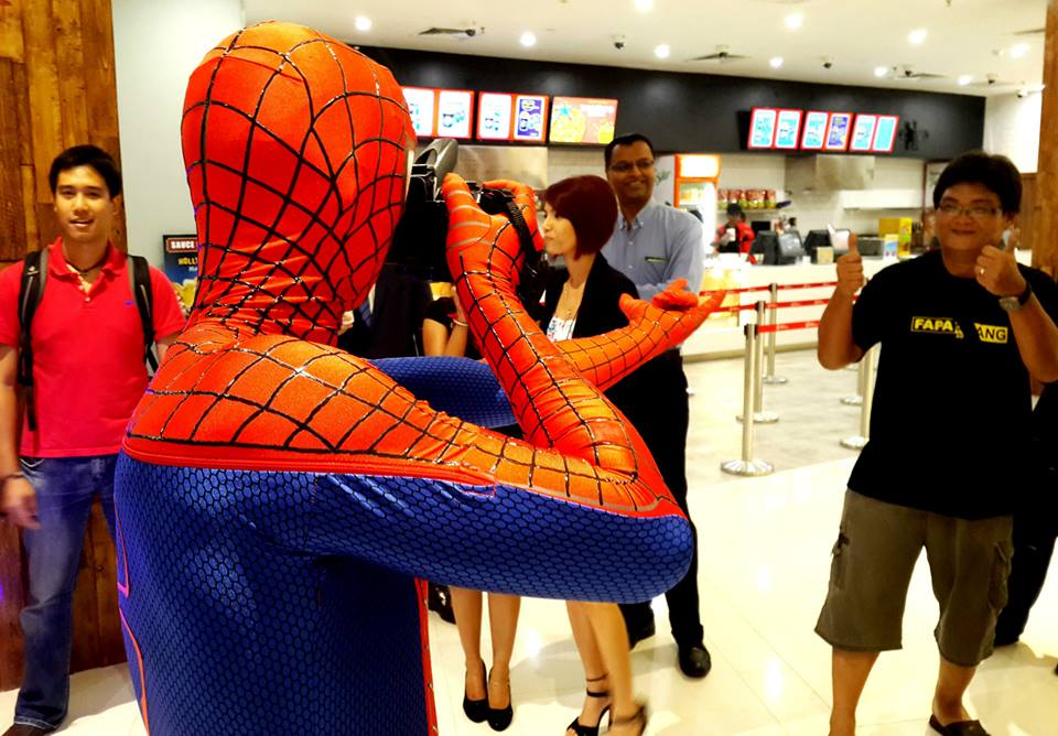 A person dressed in a Spider-Man outfit holds a camera to take a photo at 'The Amazing Spider-Man 2' premiere in Penang.