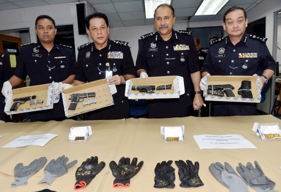 Mohd Bakri (2nd from left) and Johor chief of police Datuk Seri Mohd Bakri Mohd Zinin (third from left) showing the media at the police headquarters in Johor Baru the weapons and other items seized from the three robbers.