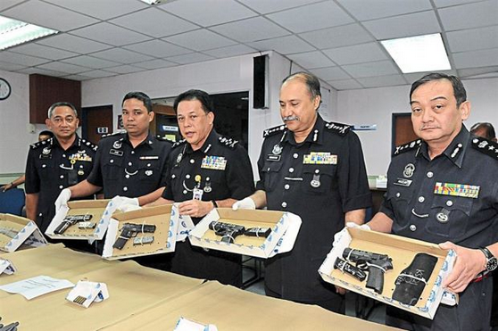 Deadly packages: Mohd Bakri (centre) with Johor police chief Senior Deputy Comm Datuk Mohd Mokhtar Mohd Shariff (second from right) and senior police officers showing the seized pistols in Johor Baru.