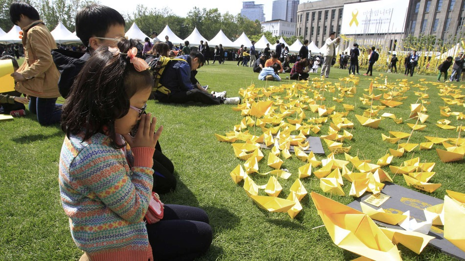 A girl prays in front of paper ships bearing messages for the victims of the sunken ferry Sewol at a group memorial altar in Seoul, South Korea, Monday, May 5, 2014