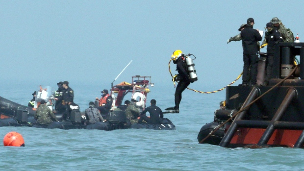 A diver jumps into the sea to look for people believed to have been trapped in the sunken Sewol ferry
