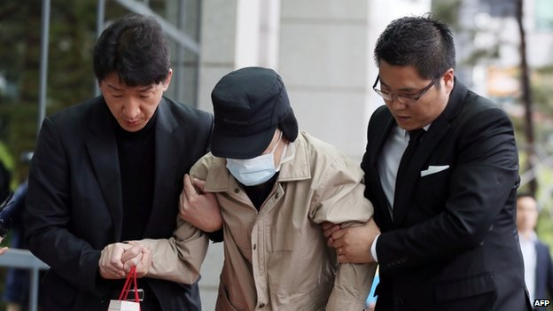 Kim Han-Sik (centre), the elderly chief executive of Chonghaejin Marine, being helped to the prosecutor's office