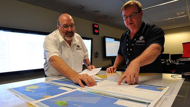 Mike Barton, rescue co-ordination chief of the Australian Maritime Safety Authority, left, looks over maps of the Indian Ocean with Alan Lloyd.
