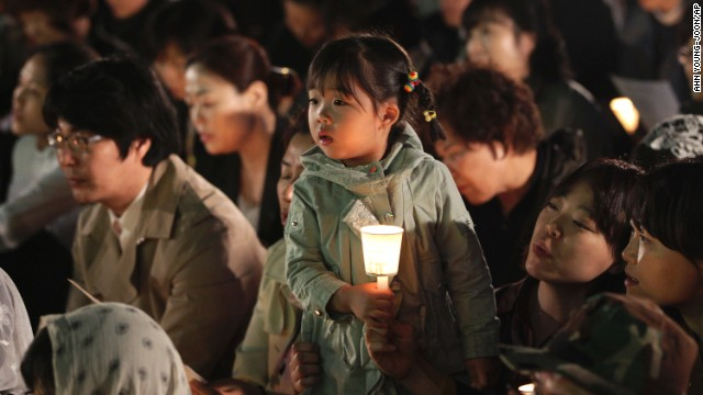 A girl in Seoul, South Korea, holds a candle during a service paying tribute to the victims of the sunken ferry Sewol on Wednesday