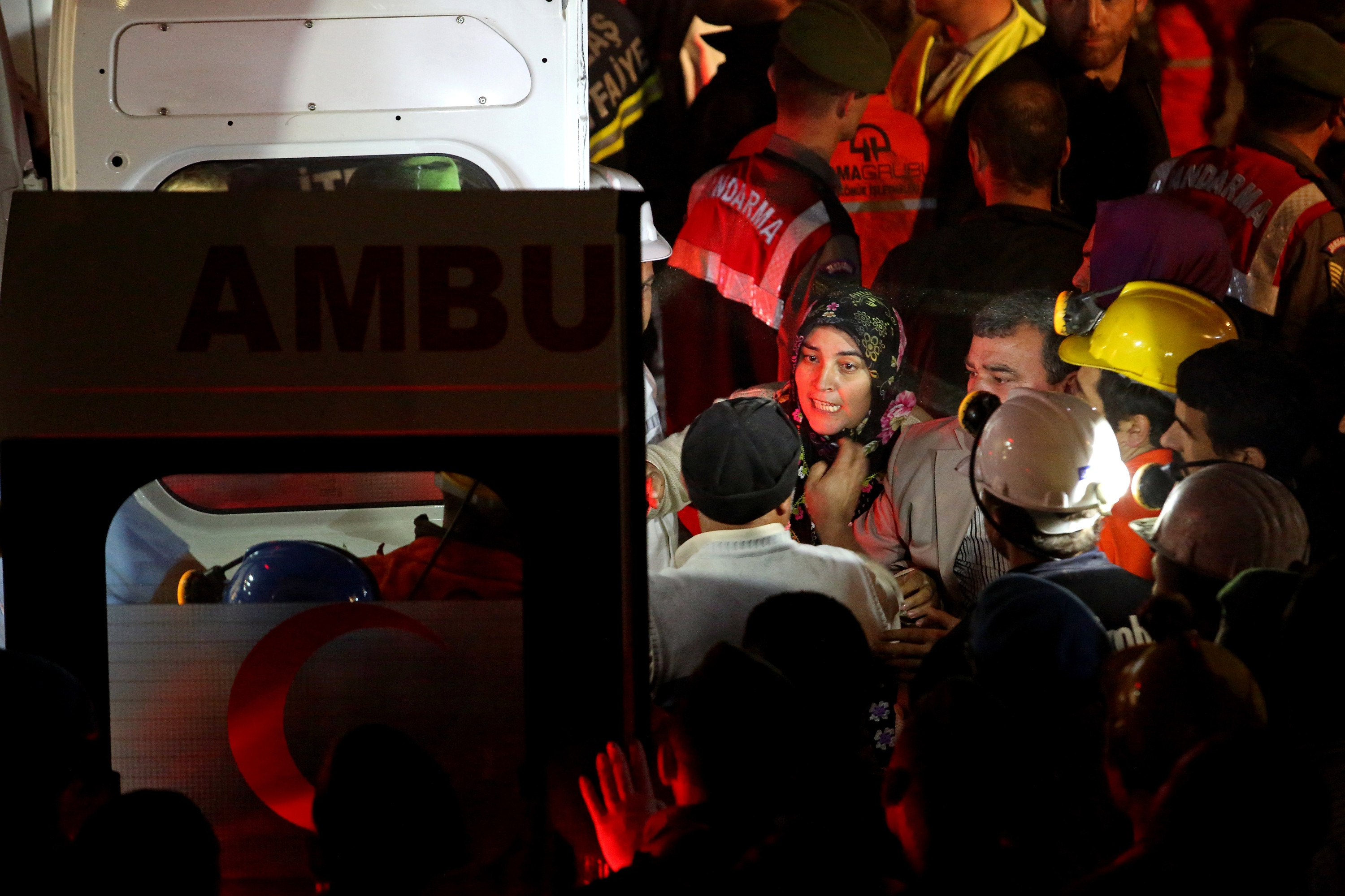 Relatives of miners who are trapped in a coal mine wait near an ambulance on May 14, 2014 in Soma, Turkey.