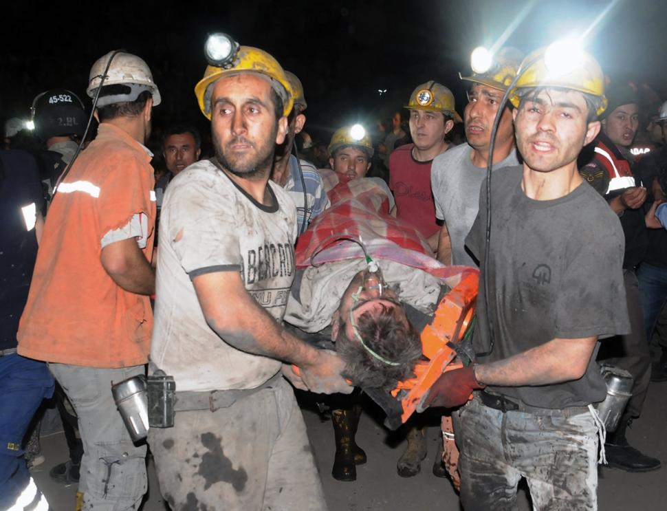 Miners carry a rescued miner after an explosion and fire at a coal mine.