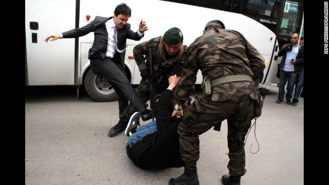 Yusuf Yerkel, an aide to Turkish Prime Minister Recep Tayyip Erdogan, kicks a person who is being wrestled to the ground by two police officers during protests in Soma, Turkey, on Wednesday, May 14. Hundreds have taken to the streets across the country since nearly 300 miners died in a mine fire near Soma on May 13, protesting the government and a lack of safety regulations. Unions have called for strikes May 15.