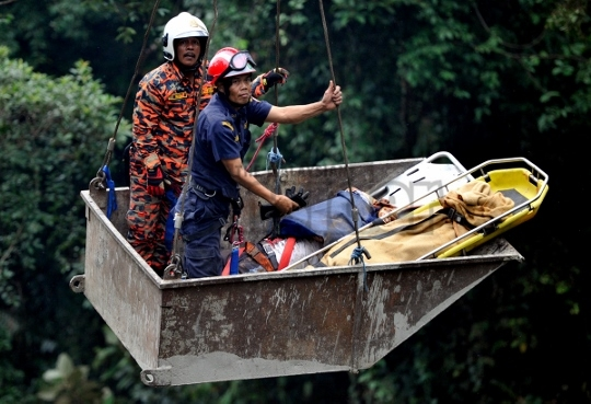 Rescuers bringing out an injured passenger from the Genting bus crash. - The Malaysian Insider pic by Najjua Zulkefli, August 21, 2013.