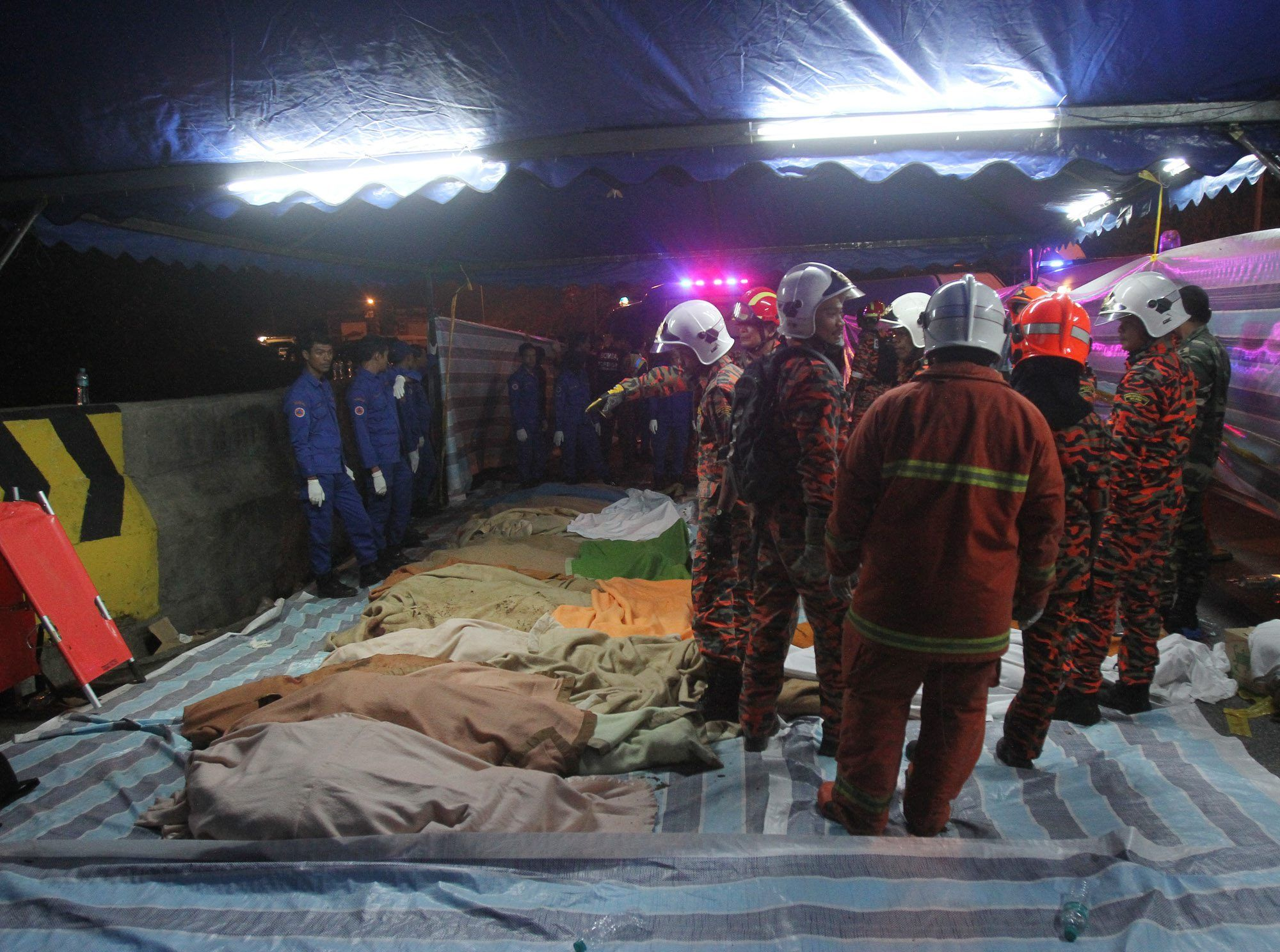 Rescuers inspecting the bodies of victims laying on the ground in Genting Highlands Wednesday.