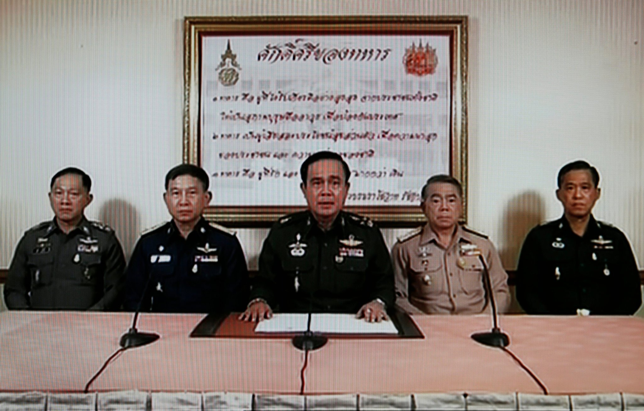 A television screenshot shows Army Chief General Prayuth Chan-ocha, center, making the announcement on Thursday.