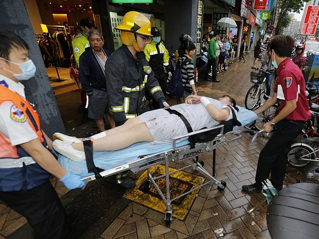 .Paramedics remove a victim from a subway station exit after the knife attack