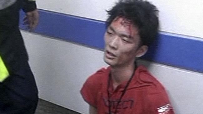 Alleged attacker Cheng Chieh, 21, is detained by police at the scene of his knife attack on a subway train in Taipei.