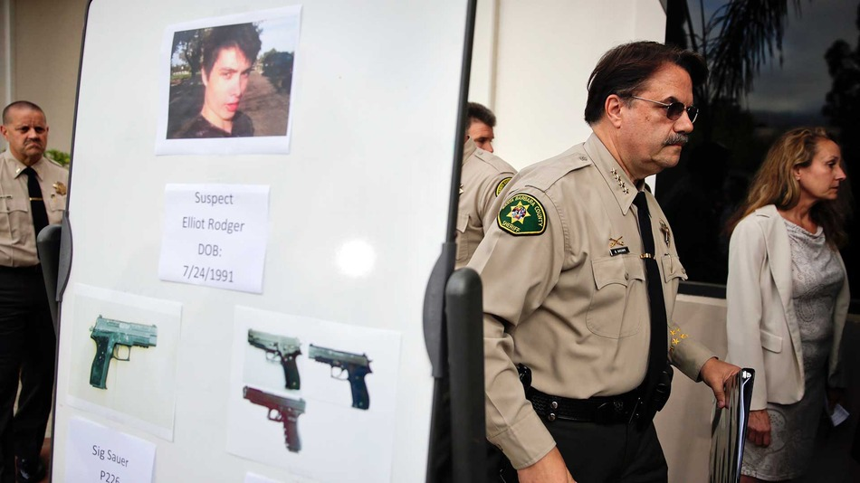 Santa Barbara County Sheriff Bill Brown, right, walks past a board showing the photos of suspected gunman Elliot Rodger and the weapons he used in Friday night's mass shooting that took place in Isla Vista, Calif., after a news conference on Saturday, May 24, 2014, in Santa Barbara, Calif. Sheriff's officials say Rodger, 22, went on a rampage near the University of California, Santa Barbara, stabbing three people to death at his apartment before shooting and killing three more in a crime spree through a nearby neighborhood.