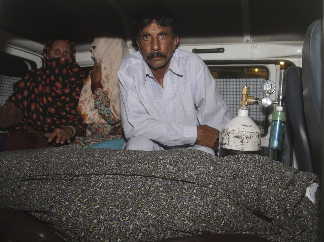 Mohammad Iqbal, right, husband of Farzana, sits in an ambulance next to the body of his pregnant wife who was stoned to death by her own family, in Lahore, Pakistan on Tuesday.
