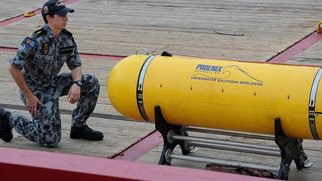 Able Seaman Matthew Tranter-Edwards kneels alongside the Phoenix Autonomous Underwater Vehicle 'Artemis' Bluefin-21, on the deck of the Australian navy ship Ocean Shield, berthed at Fleet Base West near Perth.