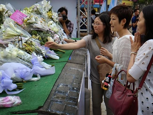 Visitors lay flowers at a makeshift memorial marking the end of the first seven days of the traditional Chinese mourning period for those killed in the last week's knife attack aboard a subway train in Taipei