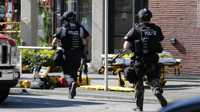 Seattle Police SWAT officers run toward a campus building after a shooting on the Seattle Pacific University campus on Thursday, June 5, in Seattle.
