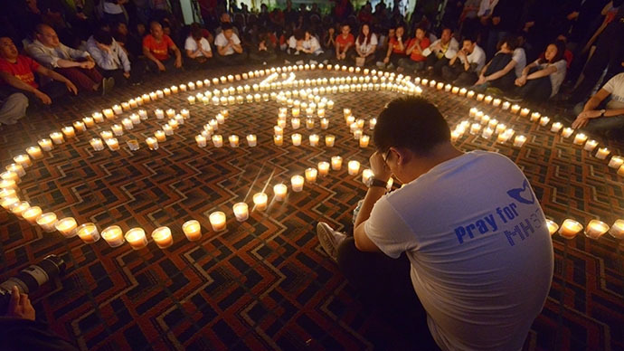 A Chinese relative of passengers on Malaysia Airlines flight MH370 prays in front of candles