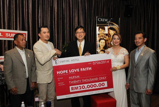 Ismail (2nd L) receives the mock cheque from Empire Hotel Director of Sales Ng Weng (3rd L).
