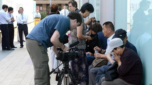 Journalists interview a group of Chinese relatives of passengers of the missing Malaysia Airlines flight MH370 as they gather outside the building housing the Malaysian Airlines office in Beijing on June 11, 2014.