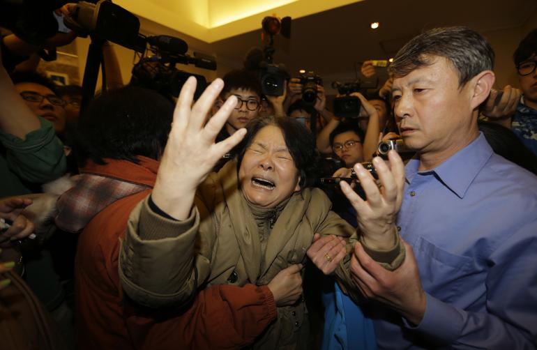 A family member of a passenger aboard Malaysia Airlines MH370 cries as she is surrounded by journalists after watching a television broadcast of a news conference, at the Lido hotel in Beijing, March 24, 2014.