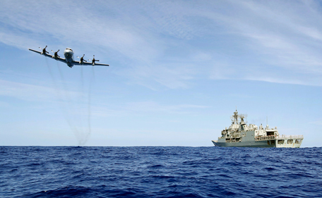 A Royal Australian Air Force (RAAF) AP-3C Orion conducts a low level fly-by before dropping supplies to Australian Navy ship HMAS Toowoomba as they continue to search for missing Malaysian Airlines flight MH370 in this picture released by the Australian Defence Force April 11, 2014.