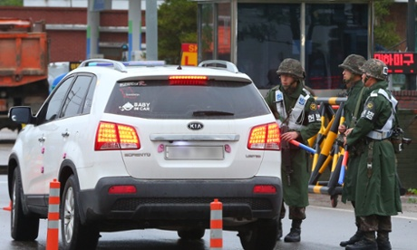 South Korean soldiers stop a car at a checkpoint amid a huge search for a sergeant who shot dead five comrades