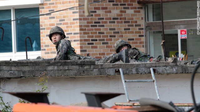 South Korean soldiers take their positions in a search for a sergeant who is on the run after allegedly shooting five of his comrades in Goseong.