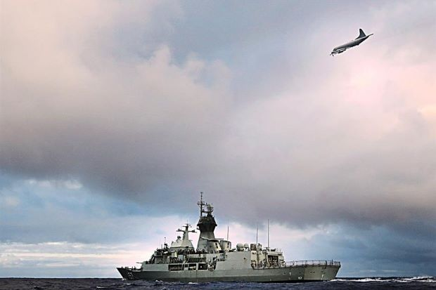 A file photo of the ship HMAS Perth transiting through the southern Indian Ocean as an Orion P-3K from the Royal New Zealand Air Force searches overhead for debris from the missing Flight MH370.