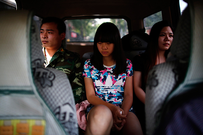 A female teacher and an instructor who is an ex-soldier, escort a girl in a car as they take her to the Qide Education Center at the request of her parents, in Beijing May 22, 2014