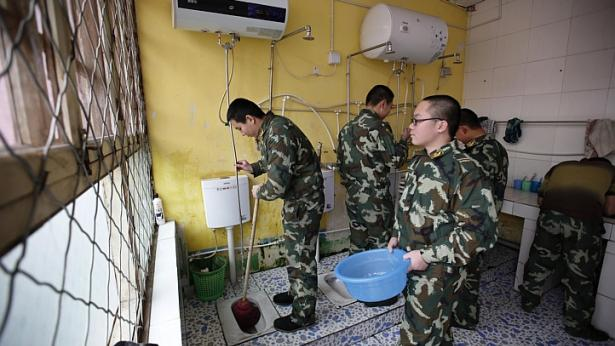 Wang (left), who was addicted to internet gaming, helps clean a bathroom in his dormitory at the Qide Education Center in Beijing on Feb 19, 2014