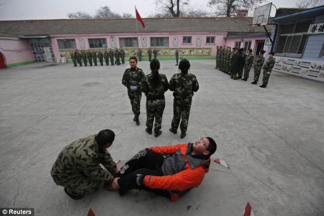 A new student practices sit-ups while other students take part in a close-order drill at the Qide Education Centre in Beijing