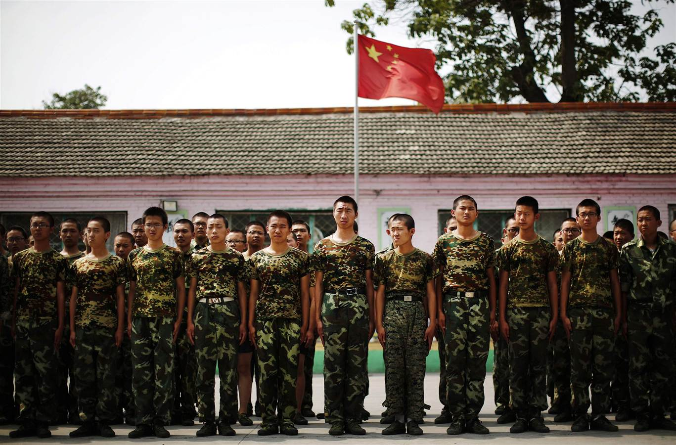 Students stand in front of the Chinese national flag as they prepare to take part in a military drill at the Qide Education Center in Beijing on June 11