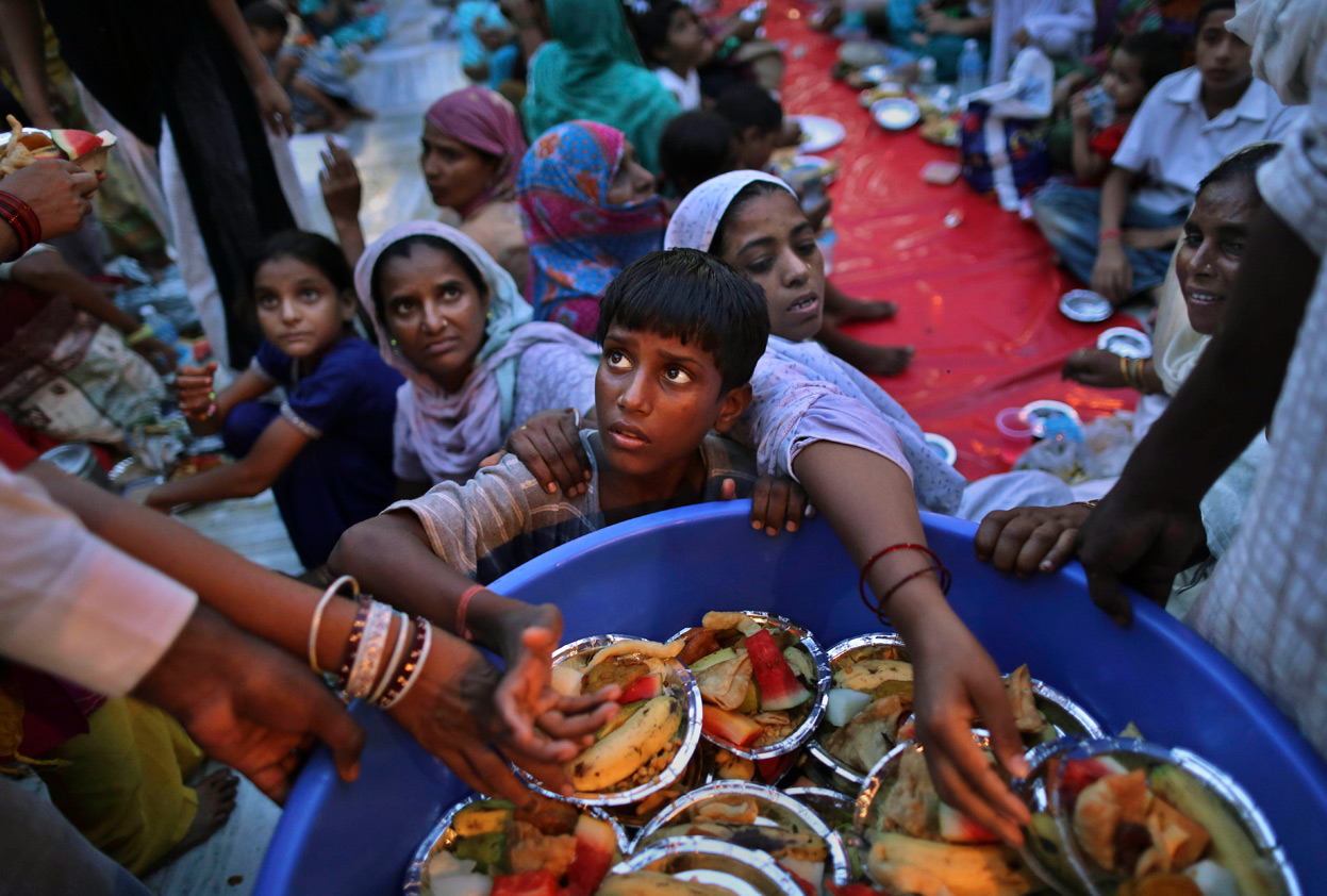 An Indian boy has his hand pushed away as he tries to take donated food from a volunteer before breaking the Ramadan fast at the shrine of Sufi saint Hazrat Nizamuddin in New Delhi, India.