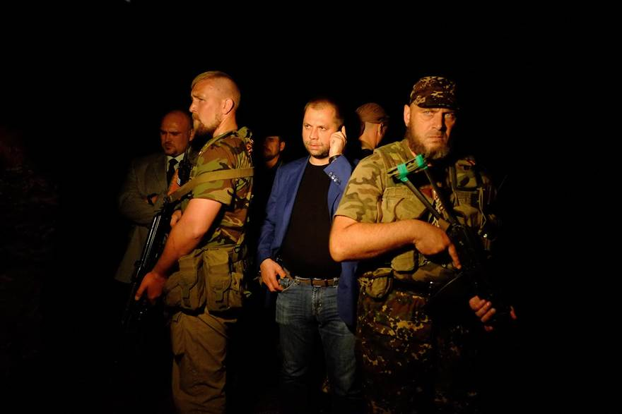"""Self-proclaimed Prime Minister of the pro-Russian separatist """"Donetsk People's Republic"""" Alexander Borodai, center, stands as he arrives on the site of the crash."""