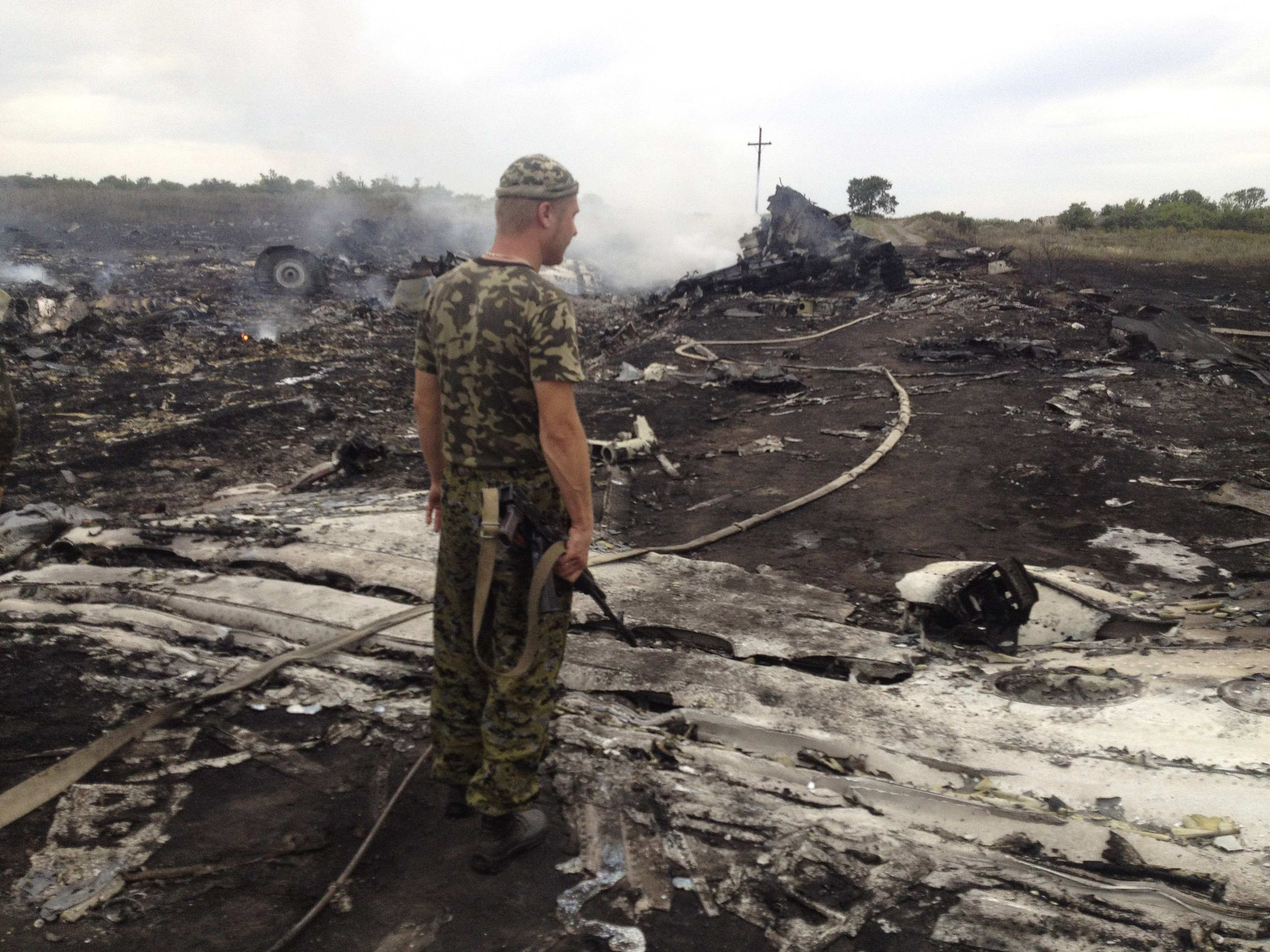 An armed pro-Russian separatist stands at a site of a Malaysia Airlines crash site.