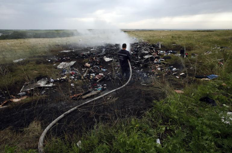 An Emergencies Ministry member works at putting out a fire at the site of a Malaysia Airlines Boeing 777 plane crash