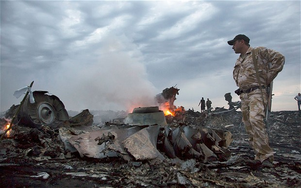 People walk among the debris at the crash site of Malaysia Airlines Flight MH17, near the village of Grabovo