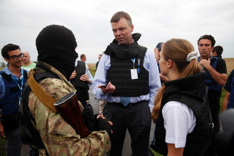 Organisation for Security and Cooperation in Europe monitors speak with a pro-Russian separatist at the crash site of Malaysia Airlines flight MH17.