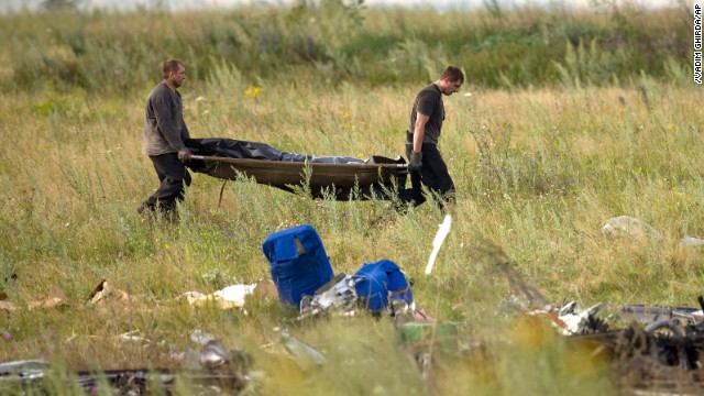 Emergency workers carry the body of a victim at the crash site of Malaysia Airlines Flight 17 in eastern Ukraine on Saturday, July 19