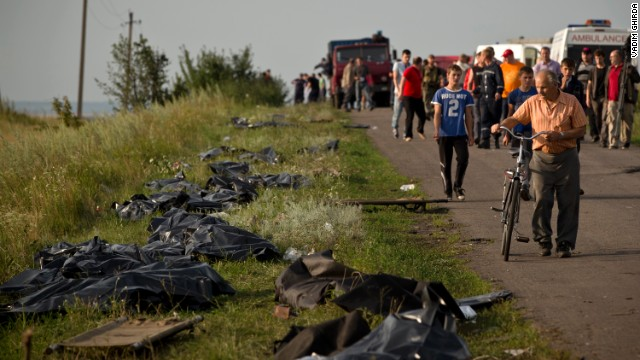 Victims' bodies are placed by the side of the road on July 19 as recovery efforts continue at the crash site. International officials lament the lack of a secured perimeter.