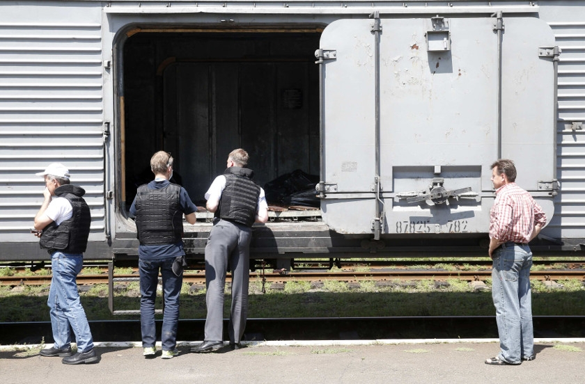 OSCE monitors inspect a refrigerator wagon which contains bodies of passengers of the crashed MAS flight MH17 in Torez, July 20, 2014.