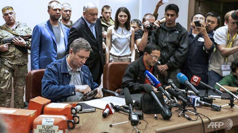 A Donetsk People's Republic official (L) and Colonel Mohamed Sakri of the Malaysian National Security Council sign documents during the handing over to Malaysia of the two black boxes recovered from the crash site of the MH17 jet at a press conference in Donetsk.