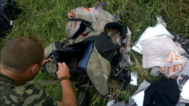 A rebel fighter is filmed rifling through the bag of one of the 298 MH17 crash victims.