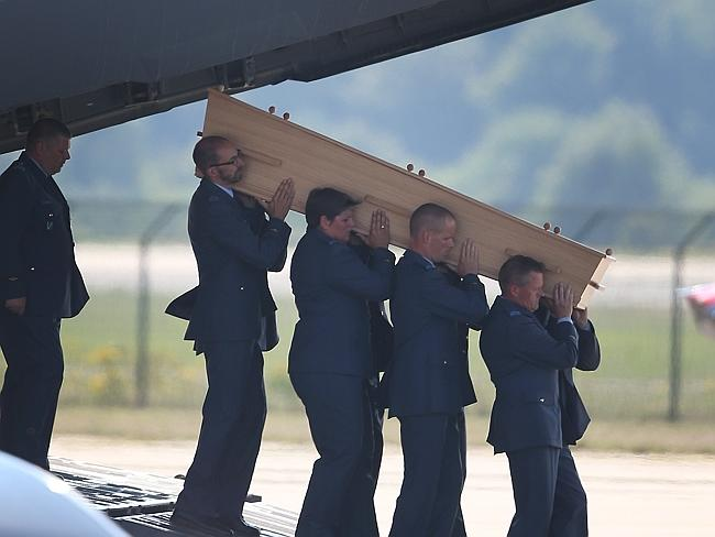 'All Australians' ... Dutch military personnel carry a coffin containing an unidentified body from a Royal Australian Air Force C-17.