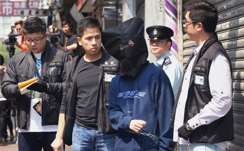 One of the suspects Henry Chau is escorted by police officers to a flat at Kok Cheung Street in Tai Kok Tsui in March, 2013.