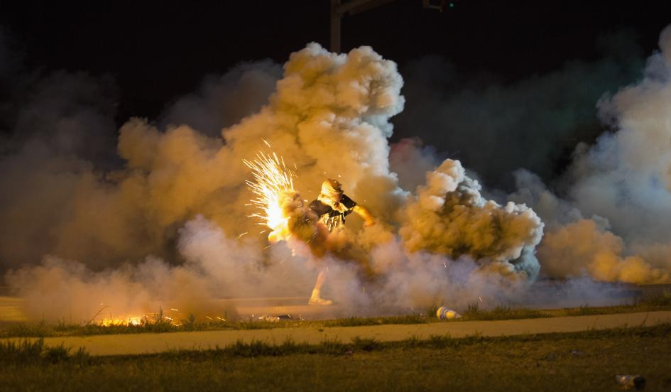 A protester throws back a smoke bomb while clashing with police in Ferguson, Missouri August 13, 2014