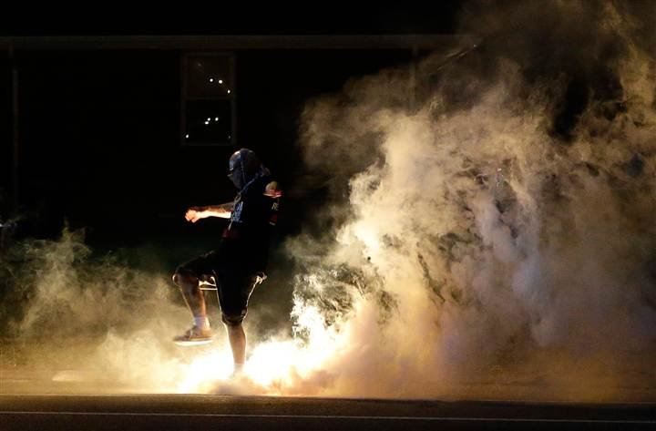 A protester kicks a smoke grenade that had been deployed by police back in their direction on Wednesday in Ferguson, Missouri.
