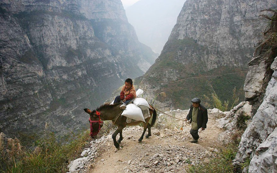 This father lets his son ride on a donkey while he walks for 5 hours into the mountains to a remote school in Gulu, China.