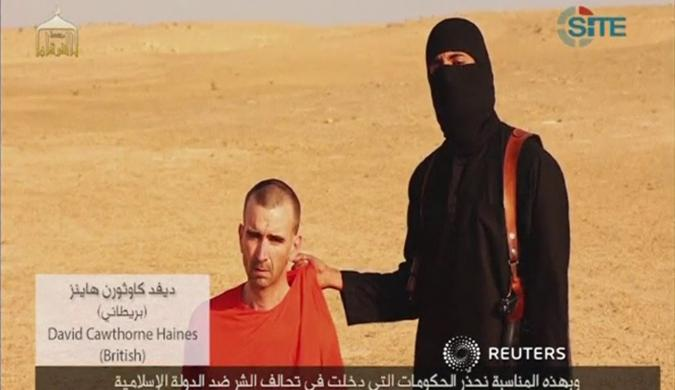 A video purportedly showing threats being made to a man Islamic State (IS) named as David Haines by a masked IS fighter in an unknown location in this still image from video released by Islamic State 2 September 2014.